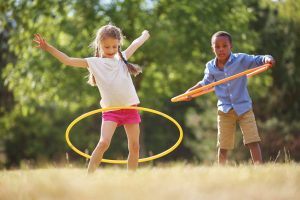 48658670 - girl and boy with hula hoop playing at the park